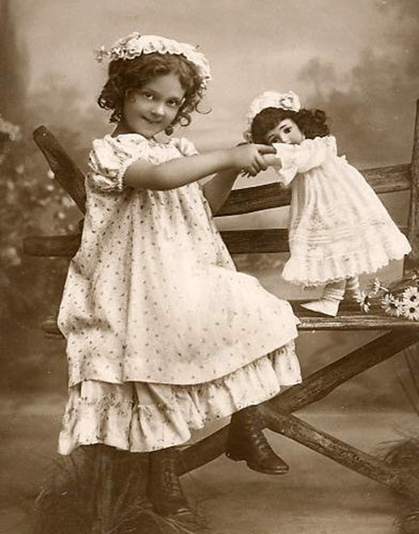 Девочка играет с куклой – винтажное фото